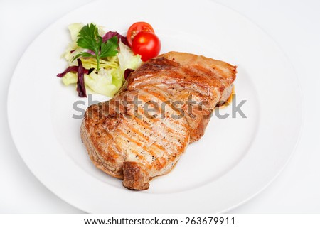 A great beef steak with vegetables on the plate.