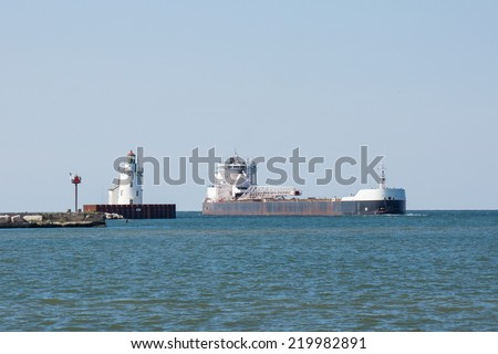 A Great Lakes bulk carrier laden with iron ore pellets passes a navigation beacon as it enters the harbor at the Port of Cleveland, Ohio on Lake Erie