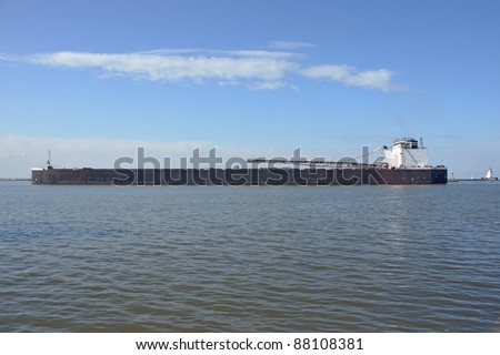 A Great Lakes self-discharging bulk freighter crosses the western basin of the harbor at Cleveland, Ohio protected from Lake Erie proper by a stone breakwater - stock photo