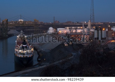 A Great Lakes self unloading dry bulk carrier ship uses its articulated conveyor boom to offload aggregate material to an ashphalt plant on the bank of the Cuyahoga River as darkness approaches - stock photo