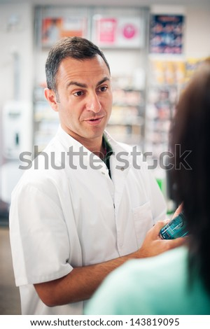 A great professional. The pharmacist resolves all doubts of his client. Photos taken on a real pharmacy. He wears a white coat as uniform