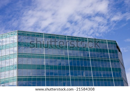 A green and blue glass building with sky and clouds reflected