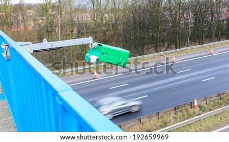 A green ANPR  camera on a UK motorway with blurred passing car