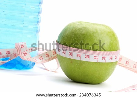 A green apple, a bottle of water and a measuring tape - stock photo