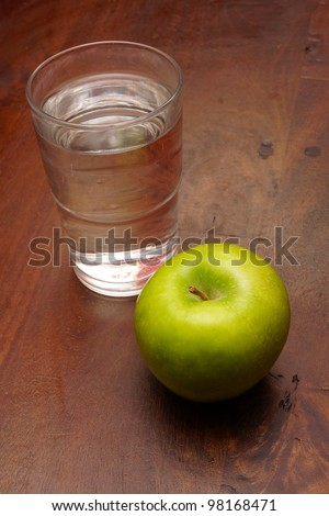 A green apple and a glass of water