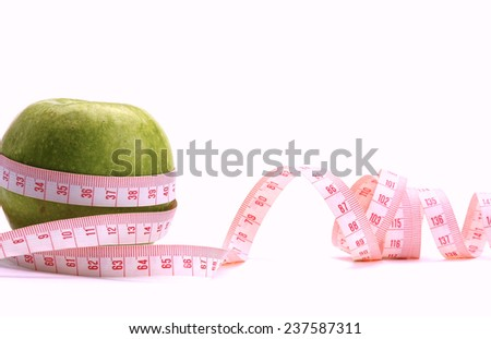 A green apple and a measurement tape, isolated on white - stock photo