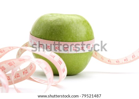 A green apple and a measuring tape, closeup, isolated on white