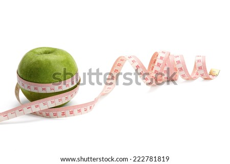 A green apple and a measuring tape, isolated on white background.