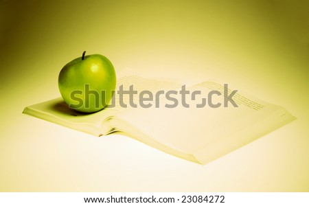A green apple and book