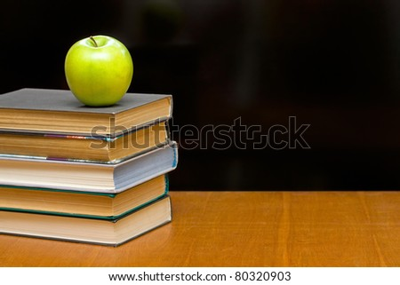A green apple and  books on the desk. Blackboard as background.