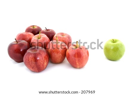 A green apple is separated from the rest - stock photo