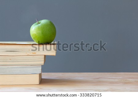 a green apple on  stack of the old books - stock photo