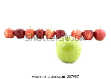 A green apple stands out from the crowd of red apples - stock photo