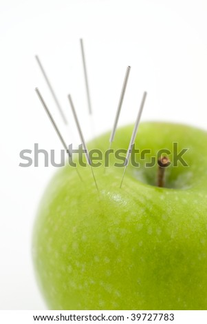 A green apple used to demonstrate the use of Acupuncture needless - stock photo
