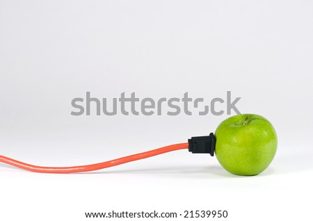 A green apple with an electrical cord plugged into it