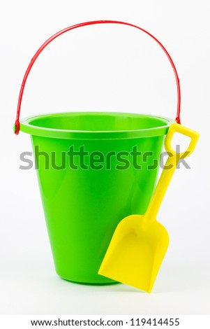 A green beach pail with a red handle and yellow shovel.