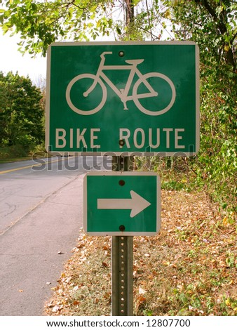 A green bike route sign on the side of the path. - stock photo
