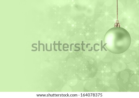 A green Christmas bauble, suspended on gold string against a star filled twinkly bokeh background, fading into solid colour to provide copy space on the left side.