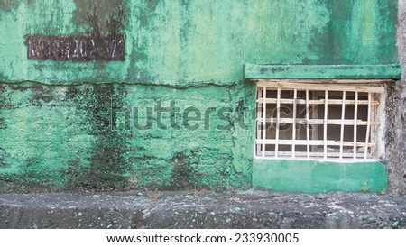 A Green Concrete Wall of The Jail of Former Military Correction Facility. The Window is Sealed With Iron Bars. On The Upper Left , There are Numbers of A Code, Which Is Peeling and Weathered. - stock photo
