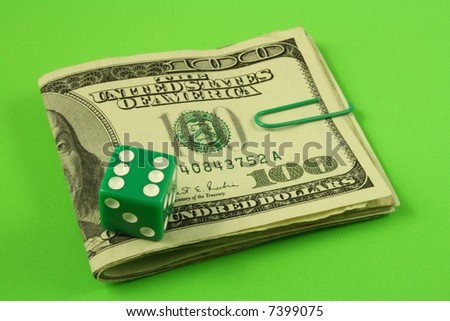 a green dice over several folded bills of one hundred dollars