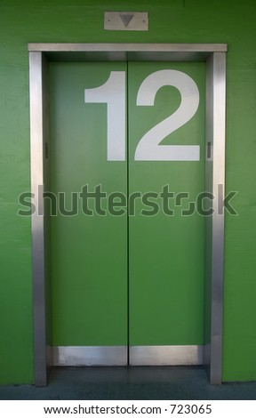 A green elevator with the number twelve painted on it - Going up or down? - stock photo