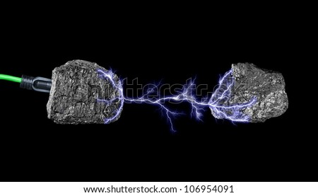 A green extension core plugged into a lump of coal and surging electricity to another piece of coal. - stock photo