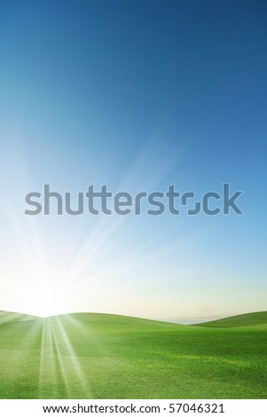 A green field with blue sky and sun-ray - stock photo