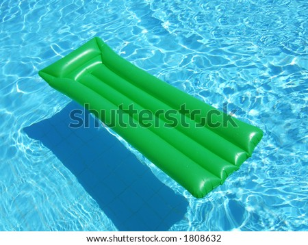 A green floating lilo on a swimming pool