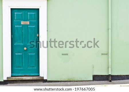 A green front door and wall in an enlgish cottage
