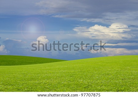 a green grass hill and blue sky background - stock photo