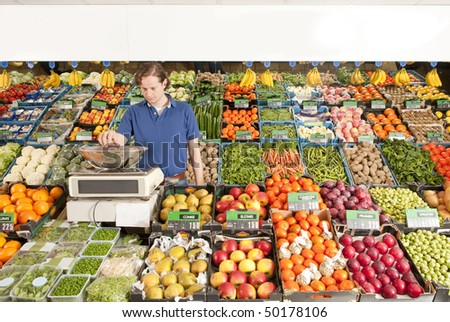 A green grocer weighing vegetables in a grocery shop - stock photo