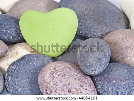 a Green heart of stone between multi colored natural stones - stock photo