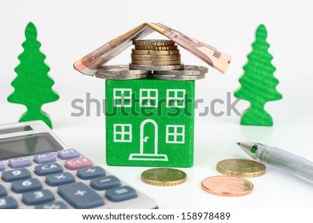 A green home with Euro money for the roof, representing savings to be made with an energy efficient home. - stock photo