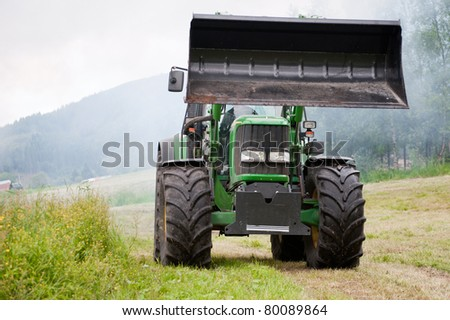 A green huge tractor driving on the field in Norway - stock photo