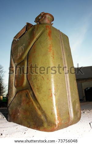 a green jerry can on concrete floor. - stock photo