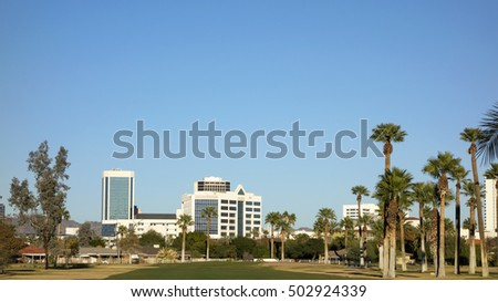 A green lawn stretching from Encanto park to downtown of Phoenix, Arizona; Copy space in clear blue sky