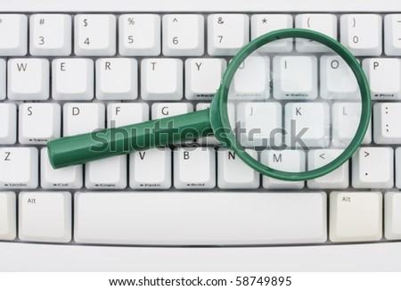 A green magnify glass on a computer keyboard, Searching on the internet - stock photo
