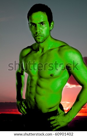 A green man in the sunset with muscles. - stock photo