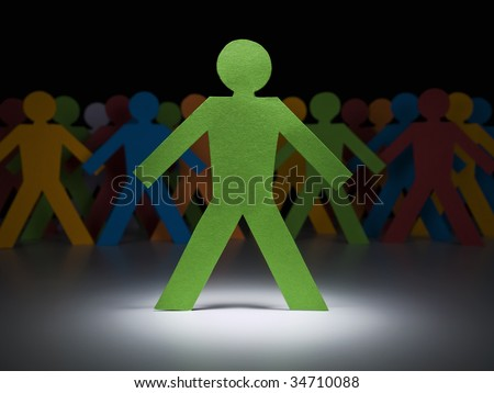 A green paper figure stands under the spotlight in front of multicolor crew. - stock photo