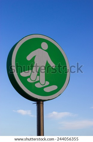 A green pedestrian crossing sign in a supermarket car park. - stock photo