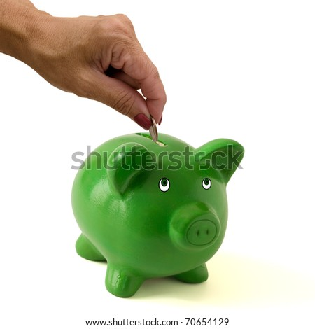 A green piggy bank with a hand putting money in it on a white background, Saving your money - stock photo