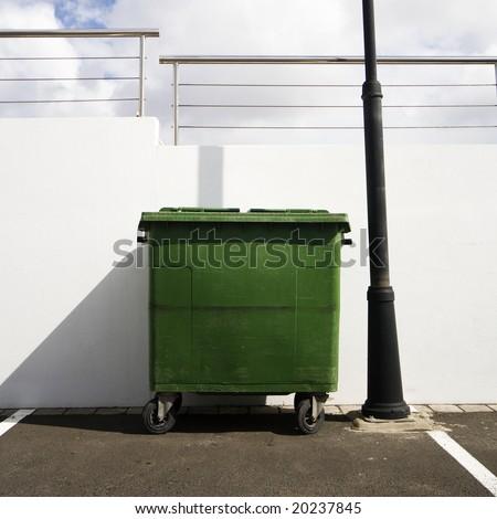 a green refuse bin. street scene - stock photo