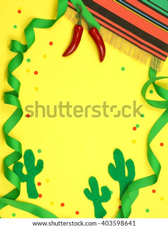 A green ribbon border winds in and out of frame and is decorated with a serape blanket, red chili peppers, felt cutout cactus shapes and confetti on a yellow background for Cinco de Mayo in May - stock photo