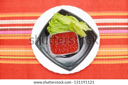 A green salad and caviar in a stylish white bowl. With rocket leaves cherry tomatoes spanish onions and capsicum. Empty white plate near. - stock photo