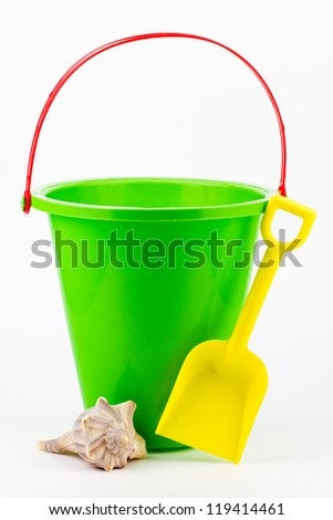 A green sand bucket with a yellow shovel and a whelk seashell. - stock photo