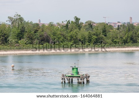 A green solar powered beacon on channel marker in canal near Venice - stock photo