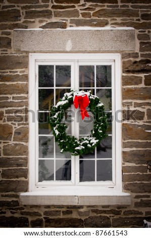A green spruce Christmas wreath with red ribbon hangs in the middle of an old, snow covered window pane set in stone wall. - stock photo