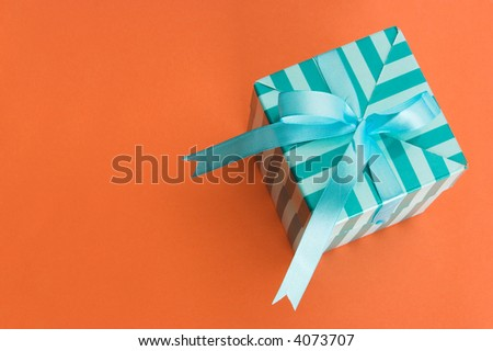 A green stripped gift box shot from above. The box is on an orange background and has a light blue/green ribbon tied in a bow on top. - stock photo