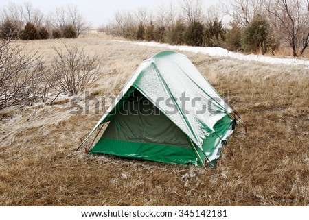 A green tent covered in snow on a cold winter's day. - stock photo
