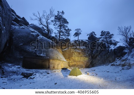 A green tent standing on the snow next to rocky cliff during an extreme winter hiking adventure in the late evening - stock photo
